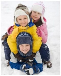 Three kids posing for a picture in snow