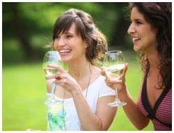 Two women drinking wine outside.