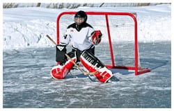 Kid playing goalie in front of hockey goal on a frozen lake.
