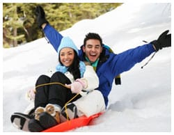Man and woman sledding down a hill