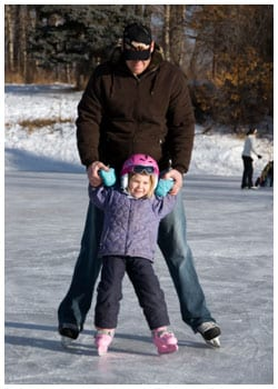 Man helping young girl to ice skate