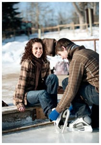 Man helping woman tie ice skates laces