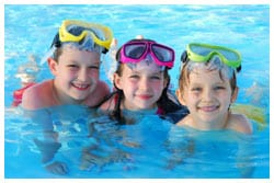 Three kids in a swimming pool wearing swimming goggles.