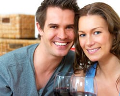 Couple posing for a picture holding wine glasses